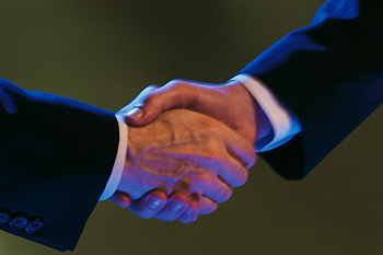 Two hands in business suits shaking hands