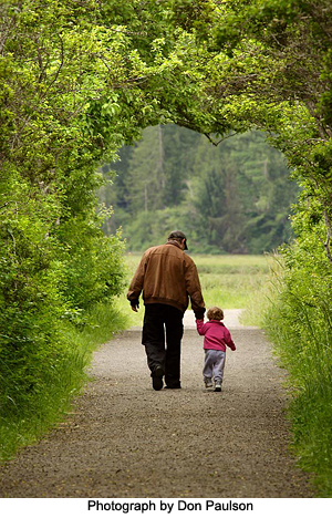 Man and child on park path by Don Paulson